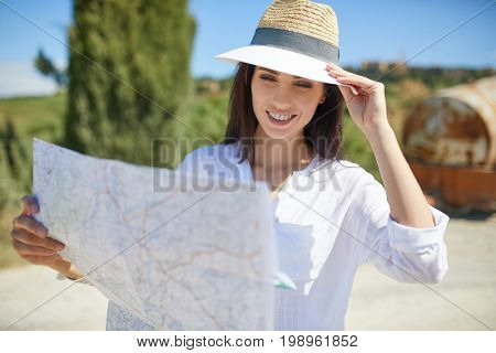A tourist with a map at the car checks the route to the destination