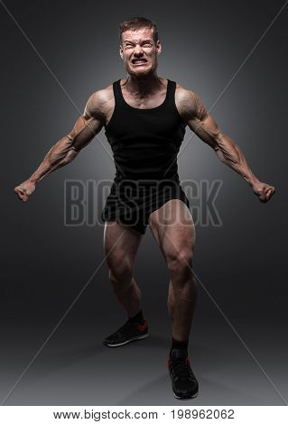 Young muscular bodybuilder posing over black background. The man in a rage very strongly strained his muscles.