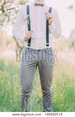 Themodern outlook of the groom in the gray pants, white shirt, suspenders with the flower accessories and wodden butterfly at the background of the spring forest