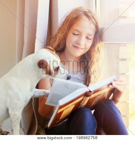 Child with dog reading book at home. Girl with pet sitting at window at read
