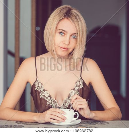 Yong woman in a home clothes drinking coffee. Woman in nightie morning