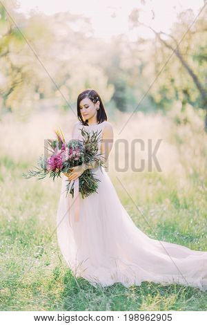 The side portrait of the bride in the wedding long white dress holding the huge bouquet of flowers at the background of the sunny park