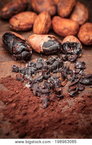 Cacao nibs on old wooden background, studio shot