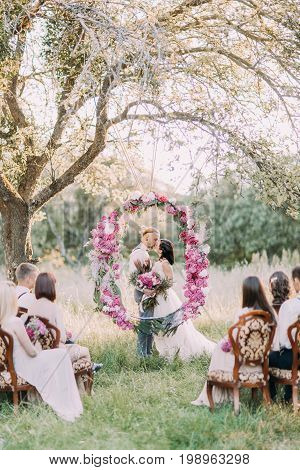 The vertical photo of the beautiful wedding ceremony in the sunny forest. The kissing newlyweds are standing behind the wedding peonies arch while guests are sitting on the chairs