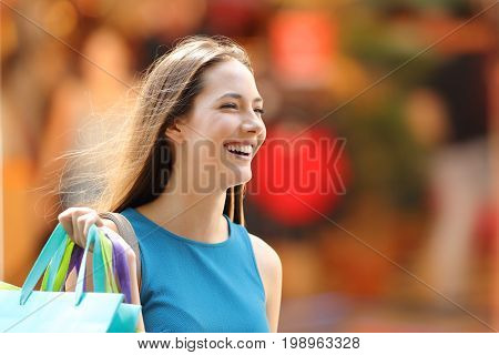 Portrait of a happy shopper with shopping bags walking on the street
