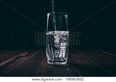 Water Poured Into A Faceted Glass On A Black Background