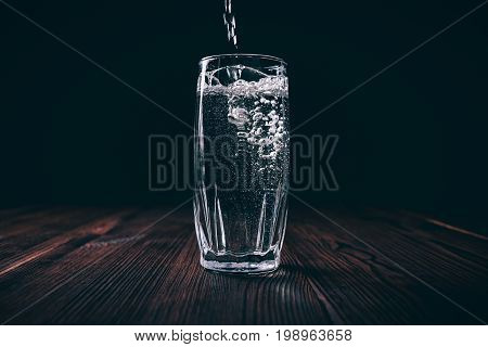 Water Pours Into A Full Faceted Glass On A Black Background