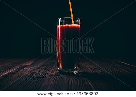 Tomato Juice Is Poured Into A Full Faceted Glass On A Black Background