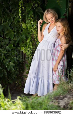 Mother and daughter posing for camera in nature. Beautiful young mom and cute daughter standing together green trees on bacground.