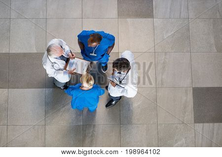 High angle view of senior doctors and young surgeons discussing over patient case. Doctors and nurses talking to each other about medical results  with copy space.
