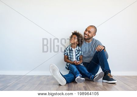 African father and his son sitting on floor and looking up in a blank wall. Happy dad and little boy sitting in an empty room. Young black man with his child thinking and pensive with copy space.
