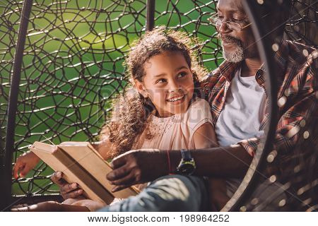 Smiling African American Granddaughter Reading Book While Sitting In Swinging Hanging Chair With Gra