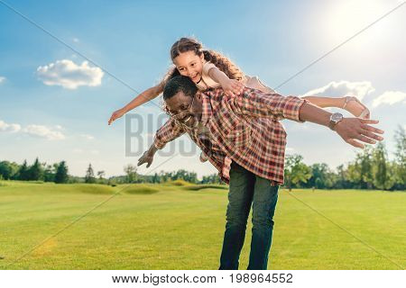 African American Grandfather Giving Granddaughter Piggyback Ride On Green Lawn With Sunlight