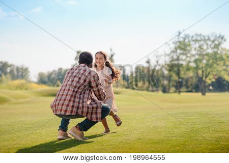 Smiling African American Granddaughter Running To Grandfather On Green Lawn In Park