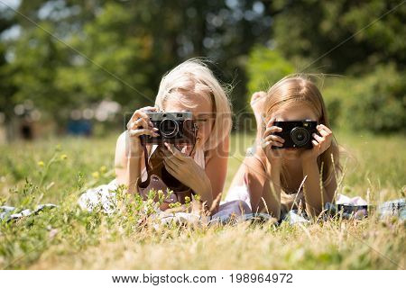 Mom and daughter taking pictures lying on blanket in park. Mother and child girl pretending to be photographers.
