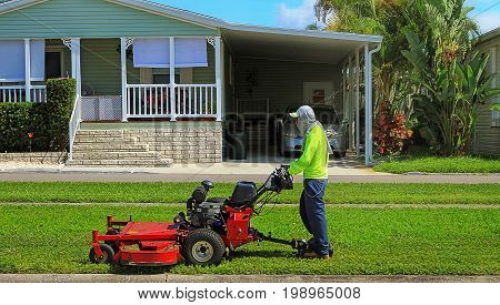 Worker handling lawn mower in public area Clearwater Tampa Florida