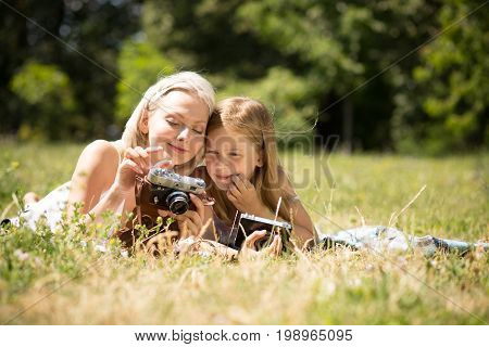 Mother teaching daughter how to take pictures on camera. Happy moments together, mom and child girl taking pictures.