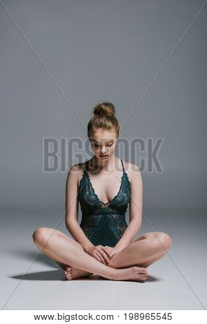 Attractive Woman With Slim Body Wearing Lace Bodysuit And Sitting In Lotos Pose On Grey