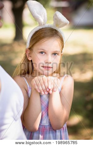 Little girl with bunny ears posing for photo. Pretty little girl wearing bunny ears, holding hands together.
