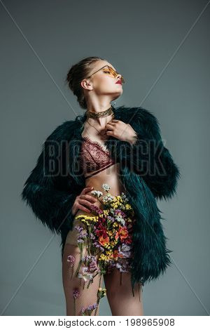 Young Sensual Model Posing In Floral Skirt, Lace Bra And Green Fur Coat For  Fashion Shoot, Isolated