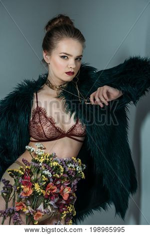 Young Sensual Beautiful Model Posing In Floral Skirt, Lace Bra And Green Fur Coat For Fashion Shoot,