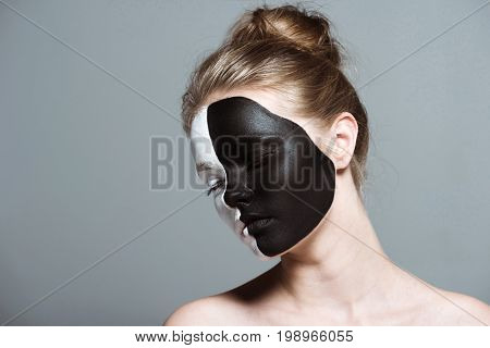 Young Beautiful Girl With Closed Eyes And Creative White And Black Bodyart On Face, Isolated On Grey