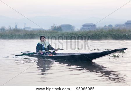NYAUNG SHWE, MYANMAR - JANUARY 12, 2012: Intha woman sailing in wooden boat on Inle lake in Shan State