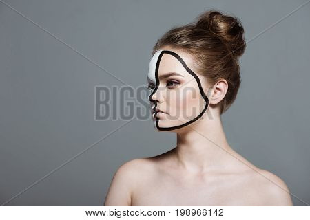 Young Beautiful Girl With Creative White And Black Bodyart On Face, Isolated On Grey