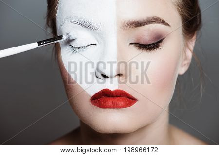 Young Beautiful Teen Girl Applying Creative White Bodyart With Makeup Brush On Face, Isolated On Gre
