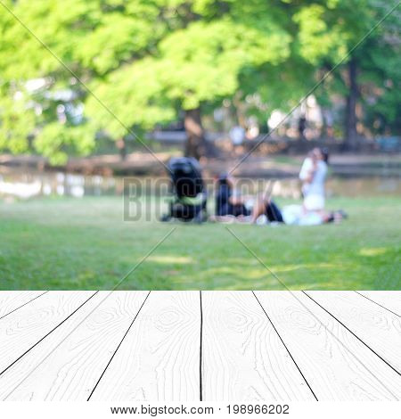 Empty perspective white wood over blur family activity at green spring park background product display montage