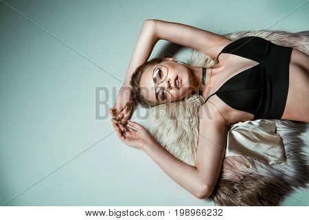 Beautiful Seductive Fashionable Young Woman Posing In Black Sexy Clothes And Fur Coat On Grey