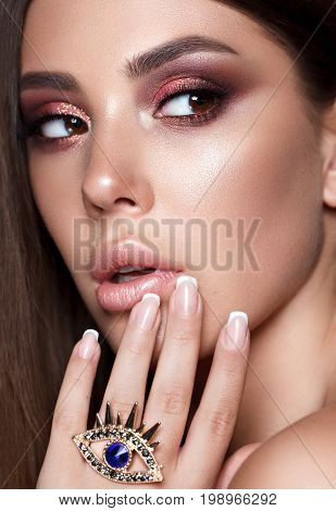 Close up portrait of beautiful young model with evening makeup, perfect taned skin. Trendy colorful smoky eyes.