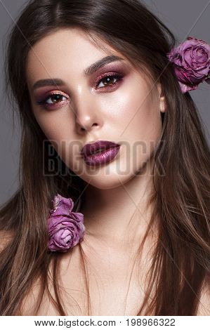 portrait of beautiful young model with evening makeup, perfect taned skin and withered lilsc roses in her hair. Trendy colorful smoky eyes. Purple lips