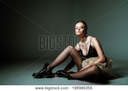 Attractive Fashionable Young Woman Posing In Black Sexy Clothes And Fur Coat On Grey