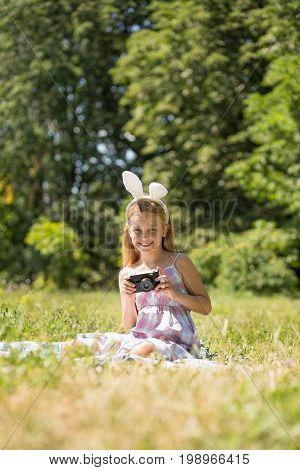 Little pretty girl sitting on blanket holding camera. Summer day, girl wearing bunny ears, smiling playing to be photographer.
