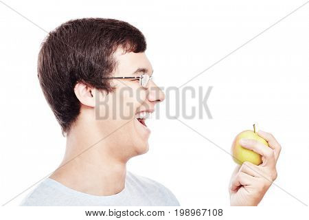 Close up portrait of young hispanic man in glasses and t-shirt laughing and holding fresh apple in his hand isolated on white background - education or healthy lifestyle concept