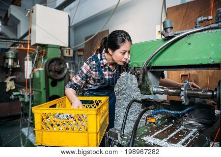 Lathe Female Worker Looking Closely At Machine