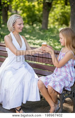 Young mother giving ice cream to her little daughter. Family harmony, mom and girl on bench, enjoying time together.