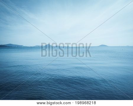 The vast blue sea with some mountains very far away
