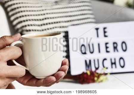 closeup of a young man with a white ceramic cup with coffee in his hand and a lightbox in the background with the text te quiero mucho, I love you so much in Spanish written in it