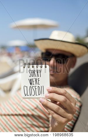 closeup of a young man wearing sunglasses and straw hat relaxing in a sunlounger in the beach showing a spiral notepad with the text sorry we are closed handwritten in the first page