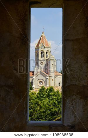 a view of the Lerins Abbey in the Saint-Honorat island, France, highlighting the lantern tower of its church, seen through an embrasure of a stone wall