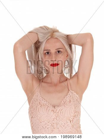 A beautiful young woman standing from the front with her both hands under her blond hair messing up isolated for white background