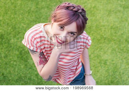 High Angle View Of Beautiful Young Woman Smiling At Camera While Standing On Green Lawn