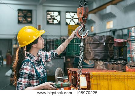 Factory Female Worker Adjusting Chain Cranes
