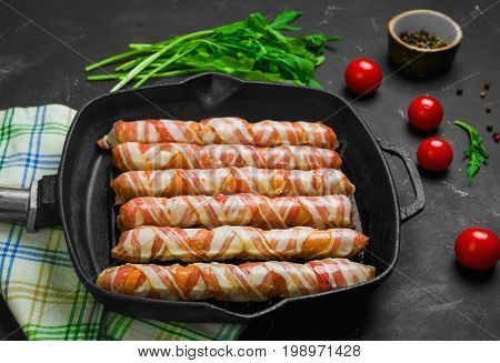 Preparation of raw sausages wrapped spirally in bacon on a cast-iron frying pan. Ingredients for sausages in bacon cherry tomatoes, rucola salad, pepper. Black concrete background. Top view, flat lay.