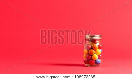 Gumballs in a jar on a red background