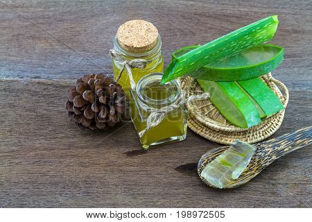 Fresh aloe vera gel on wooden spoon with aloe vera essential oil and pine on wooden table