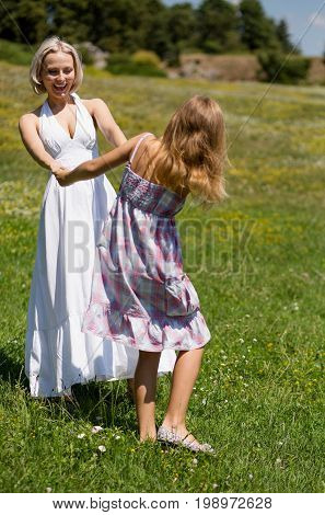 Family concept, mother spending day in nature with her girl. Mom and daughter in field having fun and dancing.