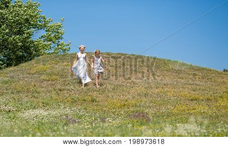 Mother and child girl, smiling, running in a meadow. Happy time together, mom and daughter enjoying summe day.